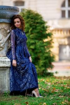 Красивая невеста в голубом платье сидит на старых зданиях