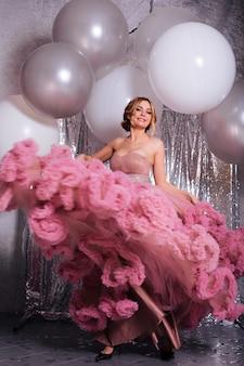 ピンクの長いドレスを着ている美しいセクシーな金髪の若い女性。魅力的なボディを持つファッショナブルな女性は、反抗的に閉じた状態を作り出します。巨乳の官能的な女の子。