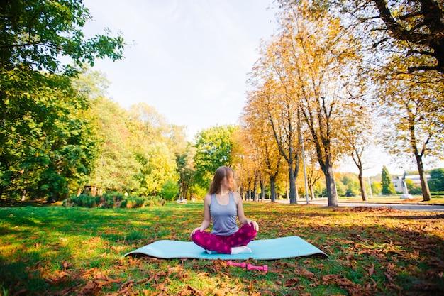 公園でヨガの練習をしているきれいな女性