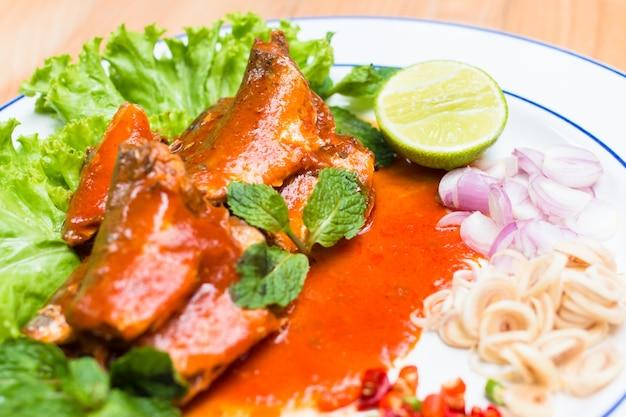 Рыба скумбрии в томатном соусе и повар в тайском остром салате.