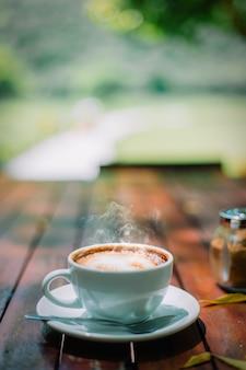 コーヒーショップの木製テーブルの上のホットコーヒーカフェラテカプチーノスパイラルフォーム