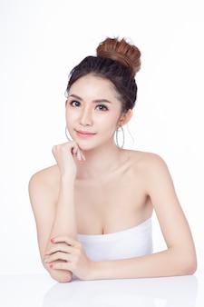 Портрет усмехаться привлекательной азиатской женщины сидя на белой предпосылке.