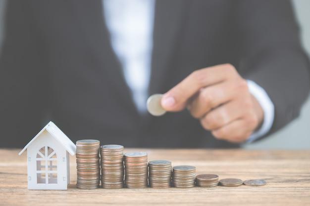 コインスタックのお金は木製テーブルの上のモデルホワイトハウスと成長の成長をステップアップします。