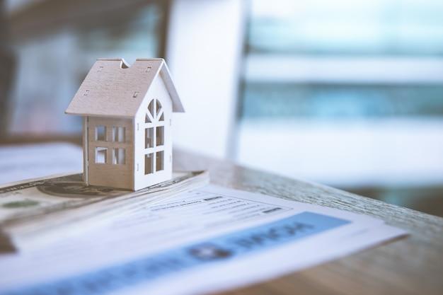 Модельный белый дом на банкноте доллара. страхование и инвестиционная недвижимость концепция недвижимости.