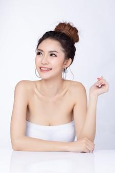 白い背景の上に座って魅力的なアジアの女性の肖像画。