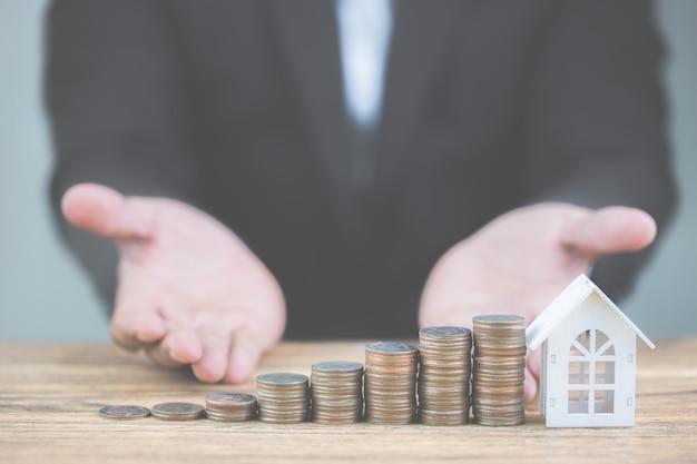 コインスタックのお金は木製テーブルの上の白いモデル家で成長の成長をステップアップします。