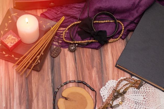 占い師の魔女。テーブルの上でろうそくが燃えています。魔法の概念、未来の予言、クリスマス。暗いキャンドルライトの背景