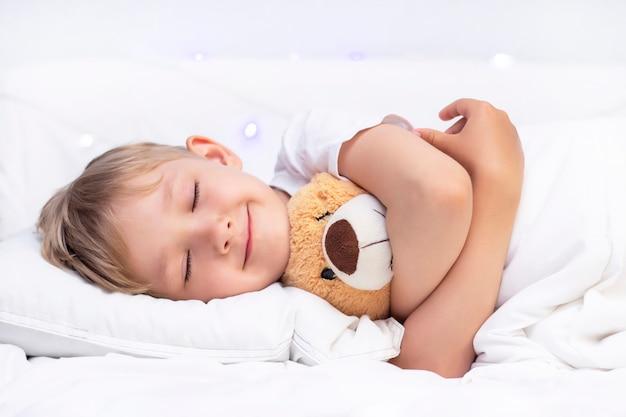 小さな白い男の子がベッドで寝ています。柔らかいおもちゃを抱擁します。