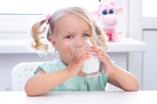 ブロンドの女の子は笑顔で牛乳を飲みます。