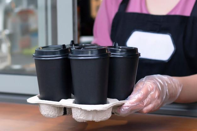 エプロンのバリスタは彼の手で紙コップにホットコーヒーを保持しています。
