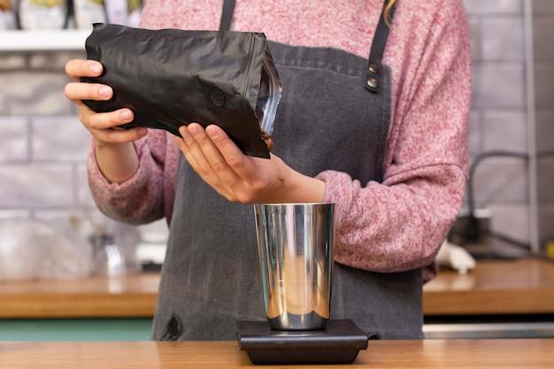 Бариста взвешивает кофейные зерна на весах.
