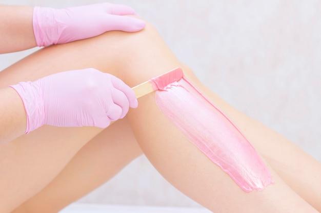ウェルネスセンターでピンクのワックスを持つ若い女性の足をワックス美容師