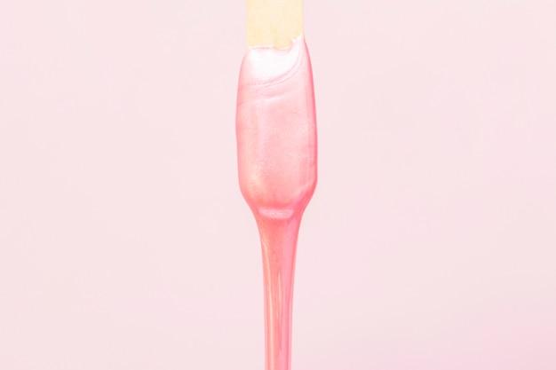 ピンクの脱毛用の液体ワックスがスティックから排出されます。