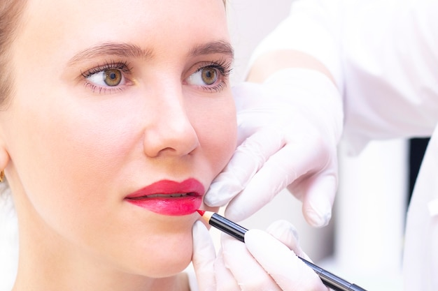 美容師サロンで彼女の唇に恒久的な化粧を持つ若い女性。白いリップペンシルで輪郭を描くアートメイク