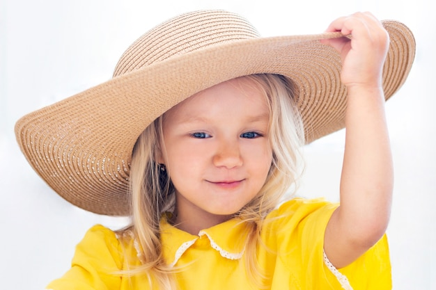 黄色の服、夏の写真で麦わら帽子の子女の子。白い背景の上