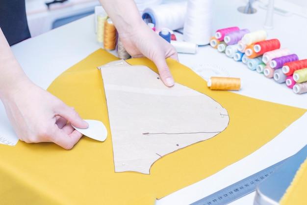 Швея обводит узор на ткани крупным планом. набор предметов для рукоделия: нитки, иголки, булавки, ножницы, рулетка и др.
