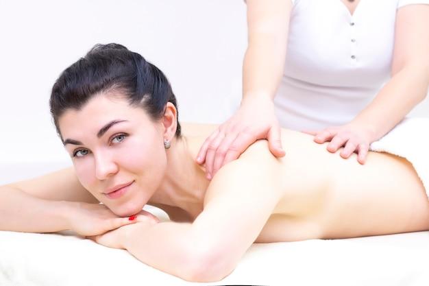 Массаж в спа салоне для девушки. концепция оздоровительного массажа. светлый фон