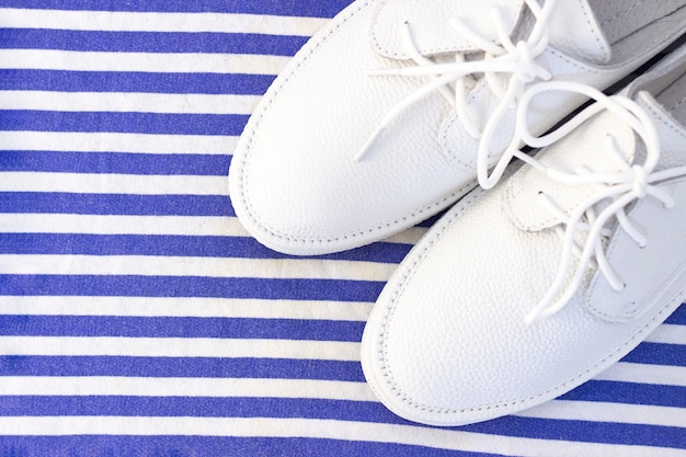 白青の縞模様の背景に白のスニッカーズ。上面図
