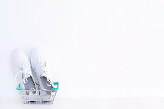Белые новые кроссовки в корзине для покупок на белом фоне.