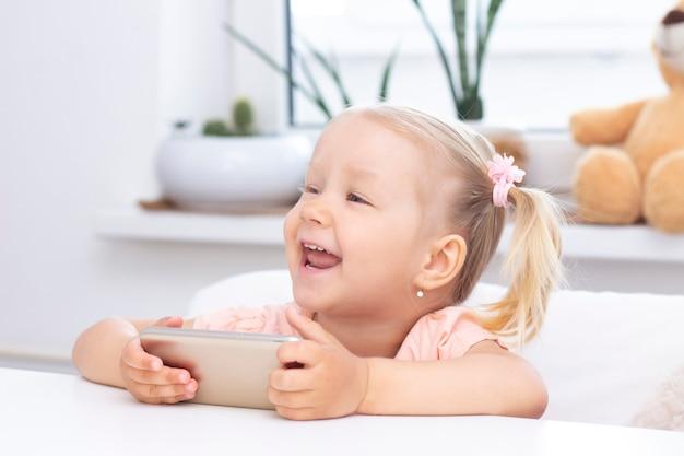 Счастливая девушка с помощью мобильного телефона, сидя дома