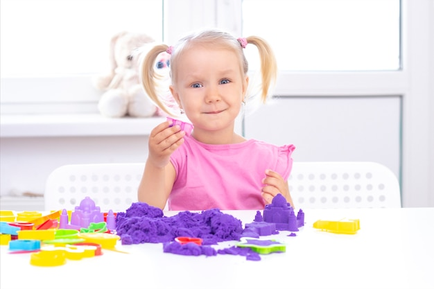 Блондинка улыбается и играет с фиолетовым песком на белом столе.