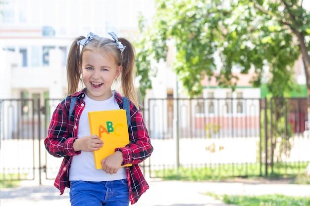 Счастливая школьница с учебником в руках. в белой футболке и клетчатой рубашке