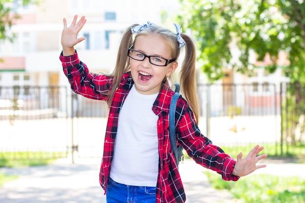 Счастливая школьница в очках на улице. в белой футболке и клетчатой рубашке