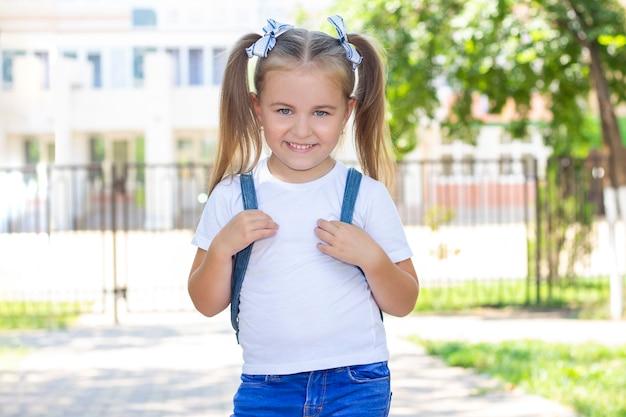 Счастливая школьница с рюкзаком. в белой футболке