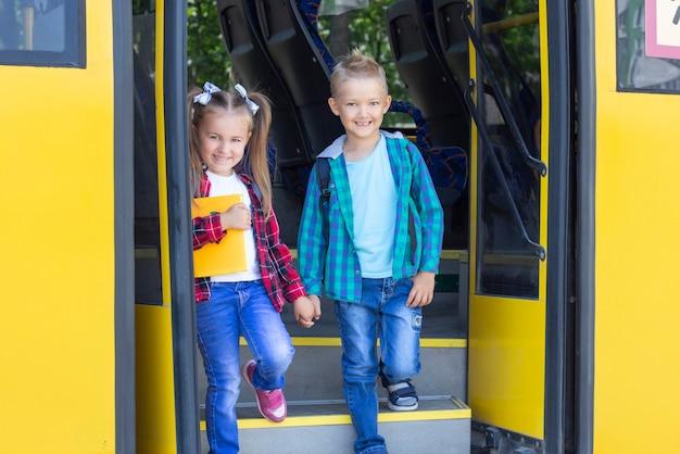 バックパックを持って幸せな小学生はスクールバスを降りる。