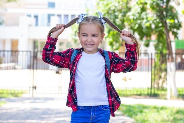 Счастливая школьница, держа ее за волосы в руках. в белой футболке и клетчатой рубашке