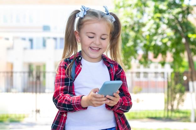 Счастливая школьница с рюкзаком разговаривает по телефону на улице. в белой футболке и клетчатой рубашке
