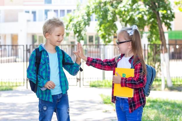 Школьники друзья с рюкзаками здороваются. школьник и школьница улыбается