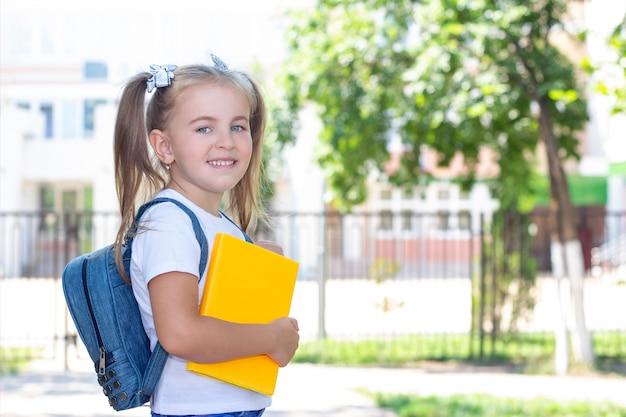 Счастливая школьница с учебником в руках.