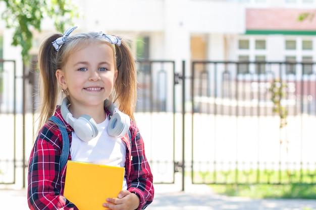 Счастливая школьница с учебником в руках. с наушниками на шее