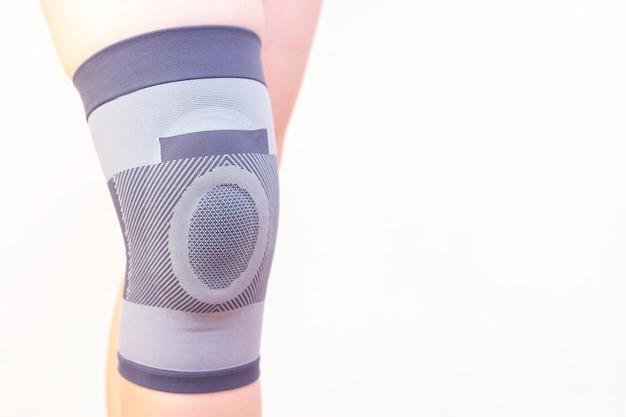 白い背景の上のブレースの膝を着ている男のクローズアップ。テキストのための場所、スペースをコピーします。痛み、膝の怪我