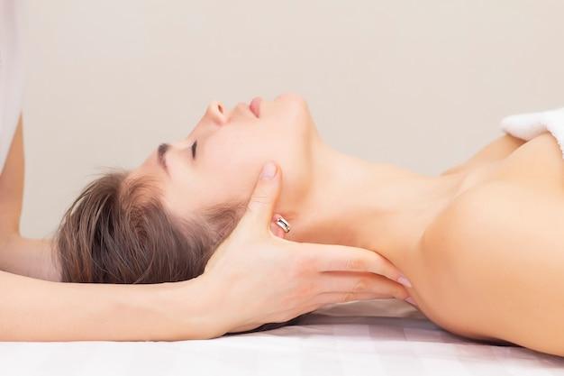 Массаж и растяжка шейных мышц. красивая девушка получает массаж в спа-салоне.