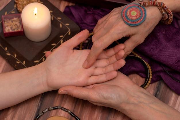 魔女占い師が女の子の手で占いを読んでいます。