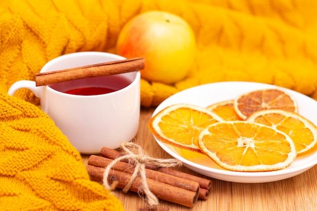 シナモンスティックと乾燥オレンジのスライスを含むホットアロマティー。木製のテーブルの上