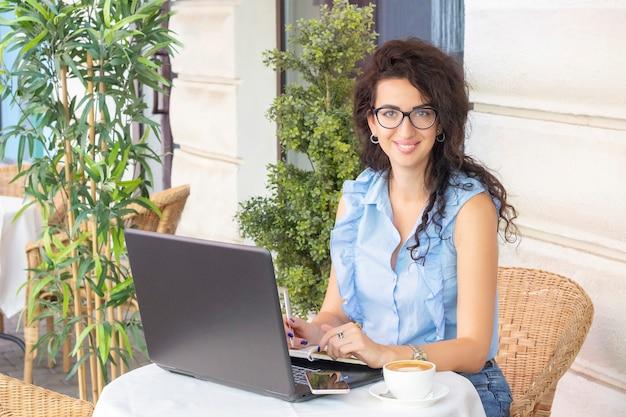カフェでノートパソコンと携帯電話でリモートで作業するガラスの女性。カフェでノートブックを使用して美しいブルネット。幸せな実業家を携帯電話で呼び出して撮影。フリーランス