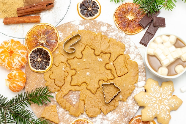 クリスマス料理。白いテーブルの上のクリスマスのベーキングおよび台所用品の食材を使った自家製ジンジャーブレッドクッキー
