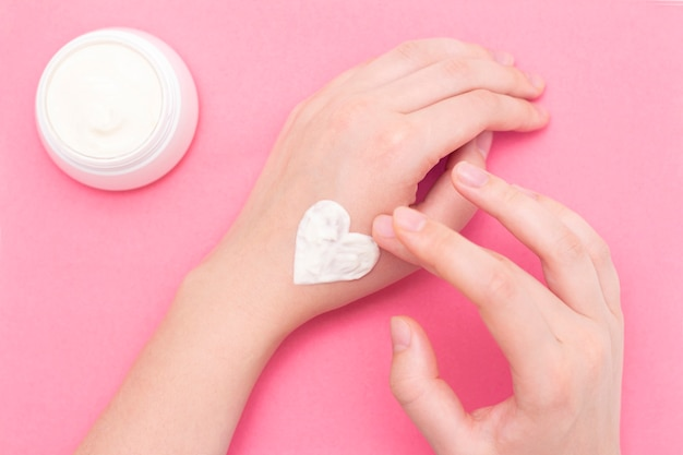 ピンクのテクスチャ背景にクリームの瓶と美しい手入れ女性の手。冬の清潔で柔らかい肌のための保湿剤。