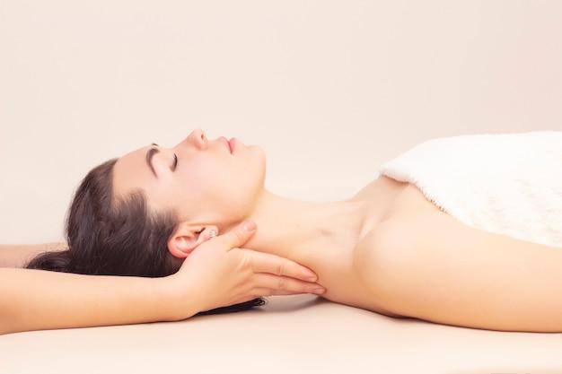 Массаж шеи в спа салоне для девочки. концепция оздоровительного массажа.