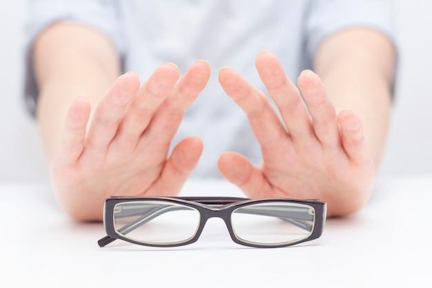 視覚に対する眼鏡の拒否。手はメガネを拒否します。メガネを掛けます。