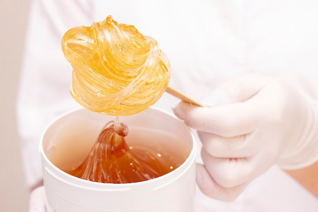 Жидкая сахарная паста или воск для депиляции на деревянной палочке крупным планом на белом фоне против формы мастера депиляции.