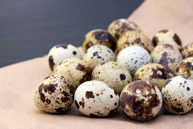 暗い上のクラフト紙のウズラの卵