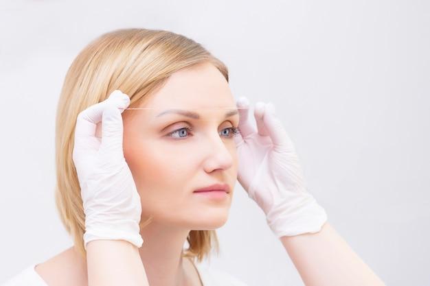 Косметолог маркирует брови с помощью ниточной татуировки бровей