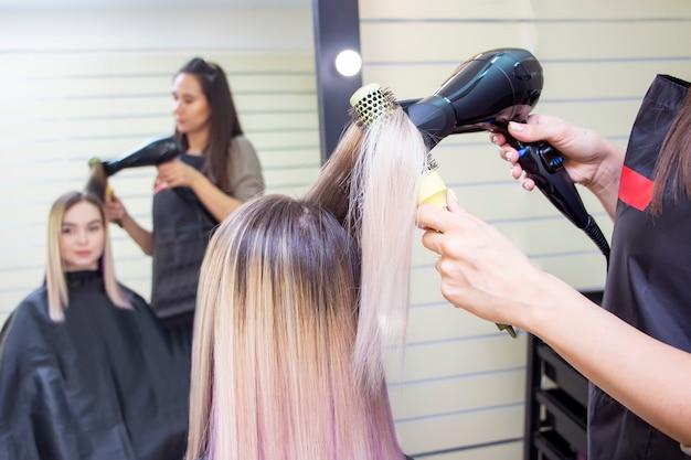 ドライヤーで髪型を作る。サロンで金髪の長い髪の少女。理髪店。
