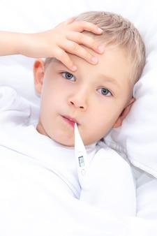 Мальчик лежит в постели с термометром во рту. концепция здравоохранения и больной ребенок, коронавирус, высокая температура,