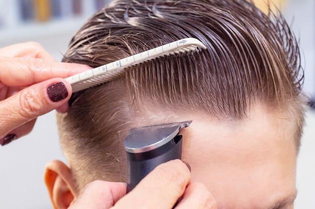 Скольжение вид сзади выстрел парикмахера с помощью машинки для стрижки волос, давая стрижку мужского пола клиента обрезанный снимок профессионального парикмахера для бритья головы до неузнаваемости молодого человека