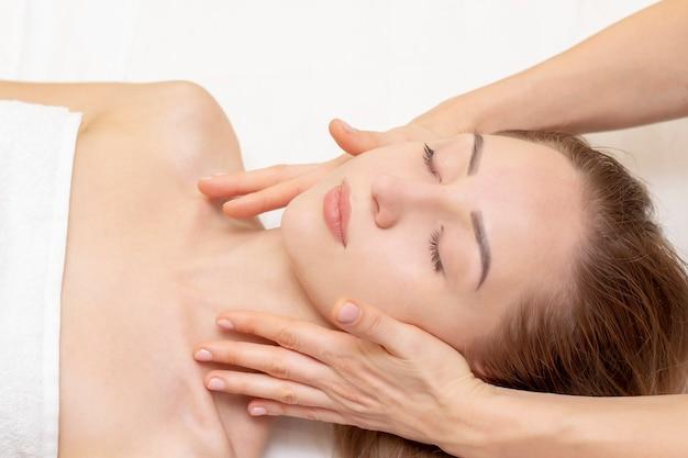 Молодая женщина, наслаждаясь массажем в спа салоне. массаж лица. крупный план молодой женщины получая обработку массажа курорта на салоне курорта красоты. уход за кожей и телом курорта. косметические процедуры для лица. косметология.